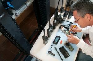 Homem realiza a manutenção de rádio comunicador
